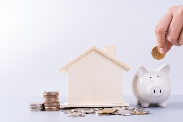 Hand putting money coin into piggy bank with wooden house and stack coins isolated grey background. property investment and house mortgage financial concept.