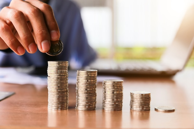 Hand putting money coins stack in saving money and growing business concept.