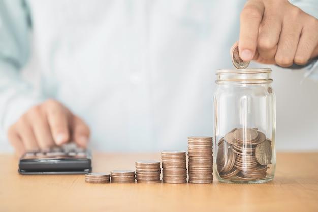 Рука кладет денежные монеты в экономную прозрачную банку и увеличивает укладку монет роста с растениями, инвестиционной прибылью и концепцией экономии денег.