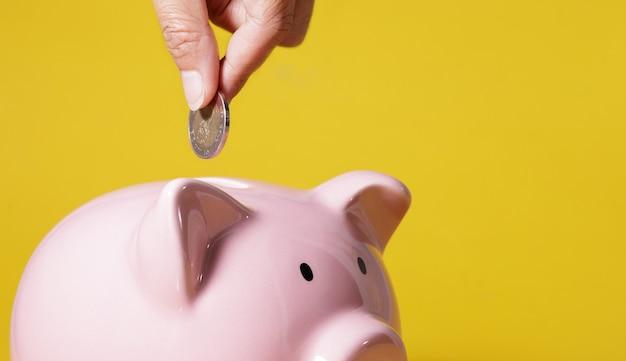 Рука кладет деньги в копилку на желтом фоне для экономики, экономит деньги, богатство и финансовую концепцию