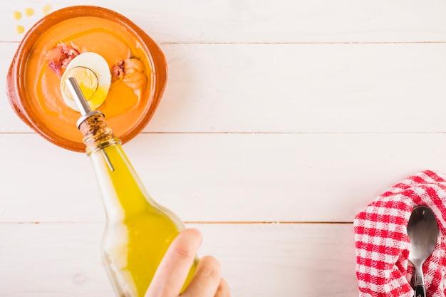 Рука, намазывающая масло на блюдо с супом