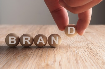 Hand putting on brand word written in wooden ball