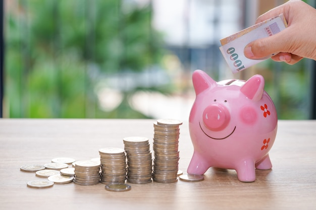 Hand putting one thousand baht into a pink piggy bank