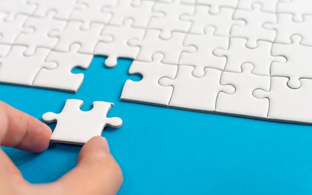 Hand putting piece of white jigsaw puzzle. team business success partnership or teamwork.
