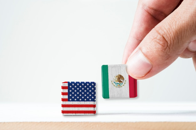 Hand putting print screen mexico flag and usa flag wooden cubic.it is symbol of conflict for both countries in mexican immigrant