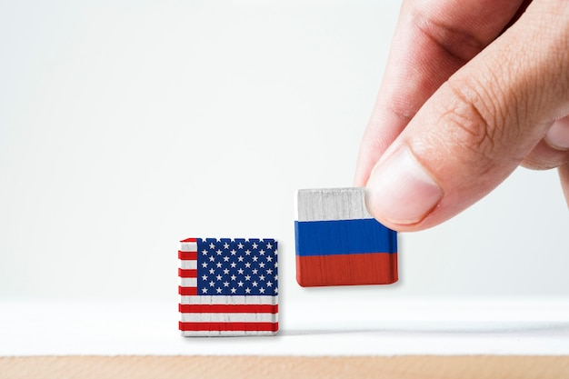 Hand putting print screen russia flag and usa flag wooden cubic.united state of america  is leader of democracy and russia is communist after world war two and cold war