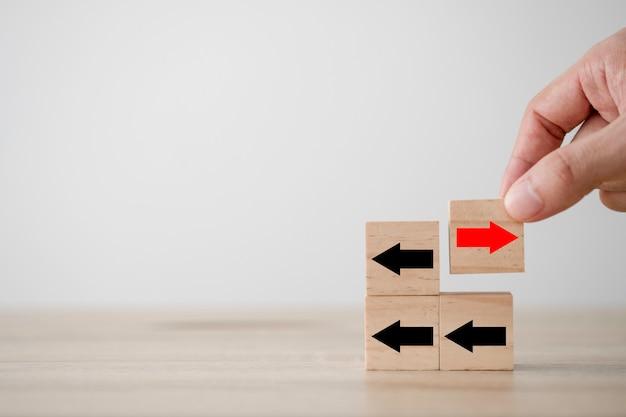 Вручите класть красную стрелку на деревянный куб который противоположное направление с черной стрелкой. разрушение и различное мышление для открытия новой технологии и новой концепции бизнес-возможностей.