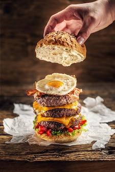 素朴な木製の環境で、ビーフパティ、卵、ピーマンを添えたトリプルチーズバーガーにパンの上部を手で置きます。