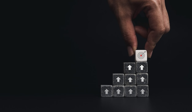Рука помещает белые кубики с целевым значком наверху черных шагов диаграммы на темном фоне с копией пространства, минимальный стиль. процесс роста бизнеса и концепция улучшения экономики.