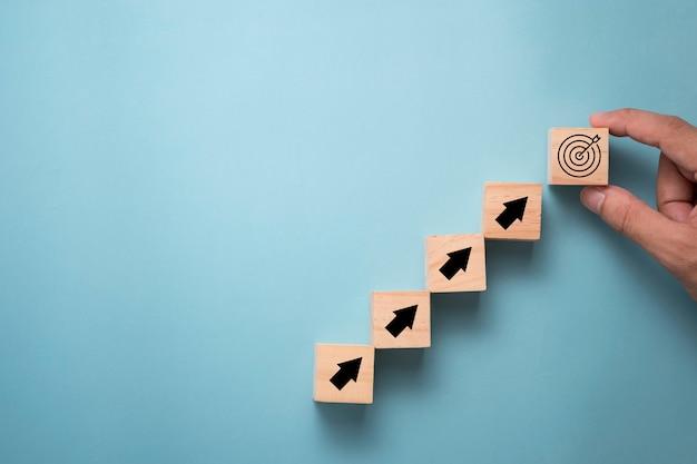 나무 큐브에 화면을 인쇄하는 가상 대상 보드와 화살표를 넣어 손. 사업 성과 목표 및 목표 대상 개념입니다.