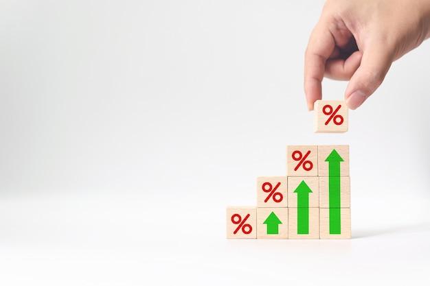 Рука кладет деревянный кубик, увеличивающийся сверху с иконкой в процентах