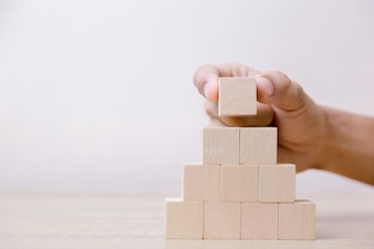 Hand putting wood cube block on top pyramid.