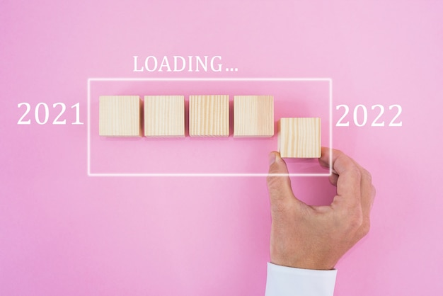 2022年までのカウントダウンのために木製の立方体を手で置く。2021年から2022年までをロードする。コンセプトを開始する