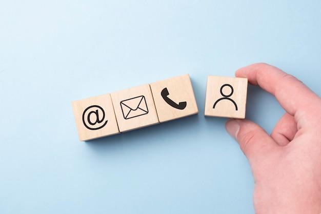 木のブロック キューブ シンボル電話、電子メール、住所、携帯電話を置く手