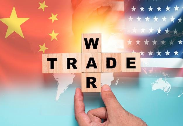 Рука помещает деревянный кубический блок для торговой войны на флаг китая и флаг сша. это символ экономической тарифной торговой войны и налогового барьера между соединенными штатами америки и китаем.