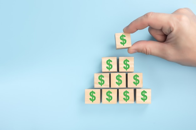 Hand putting wooden cube block on top pyramid of dollars.  business concept up trend.