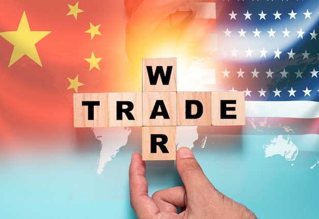 Hand putting wooden cube block for trade war on china flag and us flag.it is symbol of economic tariffs trade war and tax barrier between united states of america and china.