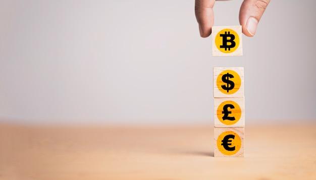 Рука помещает деревянный кубический блок, который печатает значок биткойна экрана в знак доллара, евро и фунта стерлингов, обмена криптовалюты и концепции цепочки блоков.