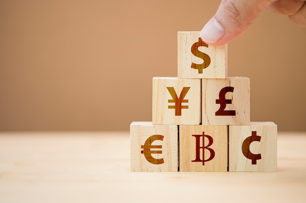 Hand putting wooden cube of us dollar sign to yuan yen euro and pound sterling sign.