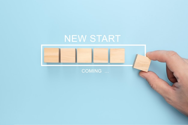 Hand putting wooden cube on virtual infographic loading bar with new start coming wording.