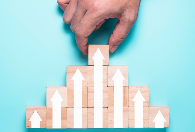 Hand putting wooden cubes block which print screen increase or up white arrow. it is symbol of economic investment profit growth.