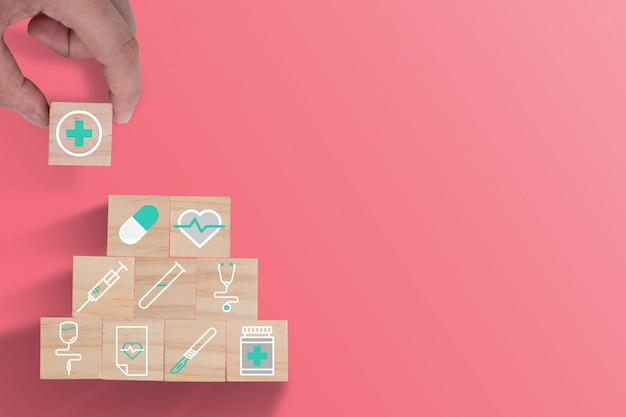 Hand putting wooden cubes stacking of healthcare medicine and hospital icon on beautiful pink background. health care insurance business and investment.