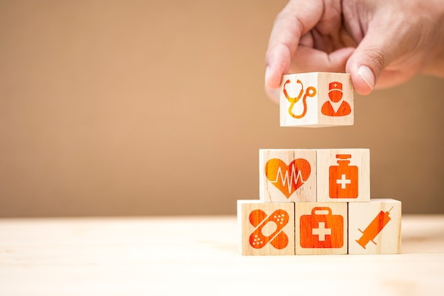 Hand putting wooden cubes stacking of healthcare medicine and hospital icon on table.