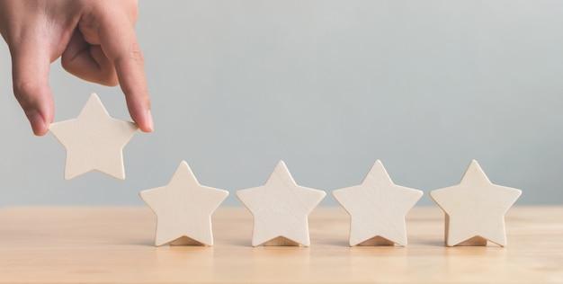 テーブルに木製の5つ星の形を置く手
