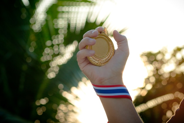 Hand raised and holding gold medal against sky sunlight.