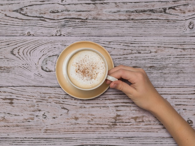 손은 나무 테이블 위에 크림과 함께 커피 컵을 발생시킵니다. 상쾌한 음료와 사랑의 개념.