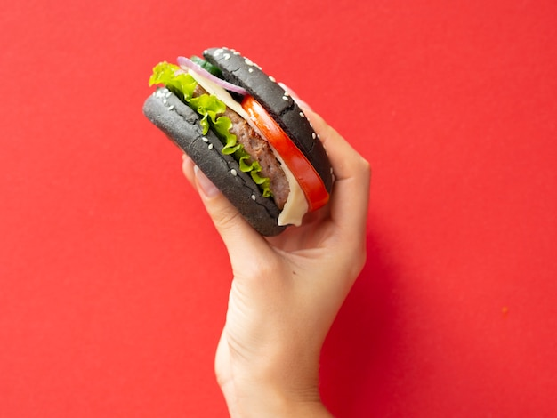 Hand raising tasty burger with red background