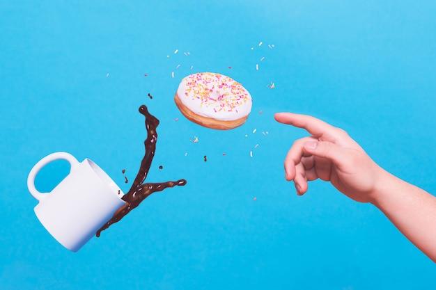 ドーナツと一杯のコーヒーに手を伸ばす手