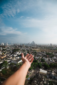 Hand reaching out towards city skyline