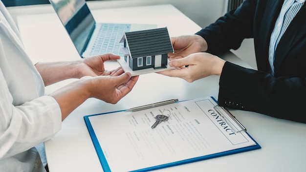 Hand a real estate agent hold the home model and explain the business contract to the buyer woman