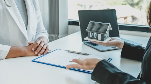 Hand a real estate agent hold the home model, and explain the business contract, rent, buy, mortgage, loan, or home insurance to the buyer woman.