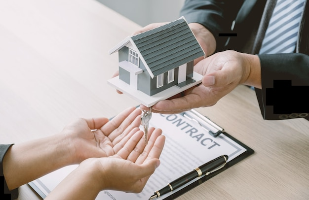 Hand a real estate agent hold the home model key and explain the business contract to buyer woman