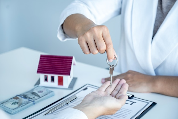 Hand of real estate agent, hold the keys, and explain the business contract, rent, buy, mortgage, loan, or home insurance.