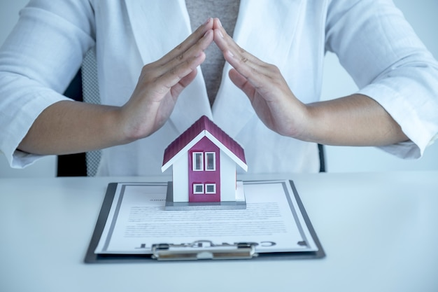 Hand a real estate agent, prevent the home model and explain the business contract, rent, buy, mortgage, loan, or home insurance.
