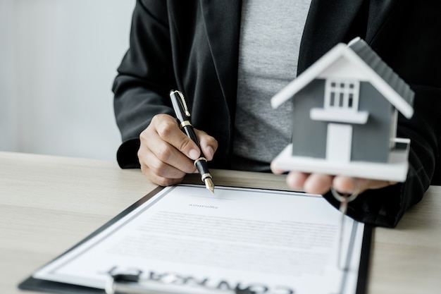 Hand a real estate agent sign with home model key and explain the business contract to buyer woman