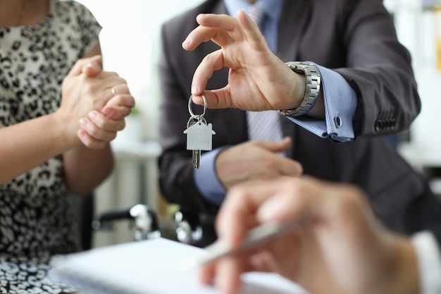 Hand of realtor hold house key aganist office