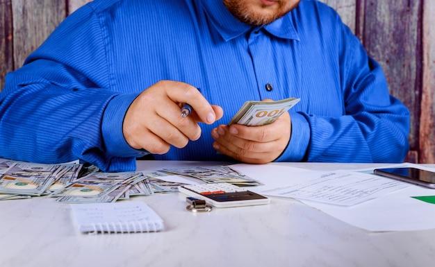 Hand recount dollars. the man counts the money new hundred-dollar bills