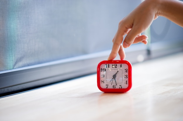Hand and red alarm clock that shows the alarm at all every morning, the concept of punctuality