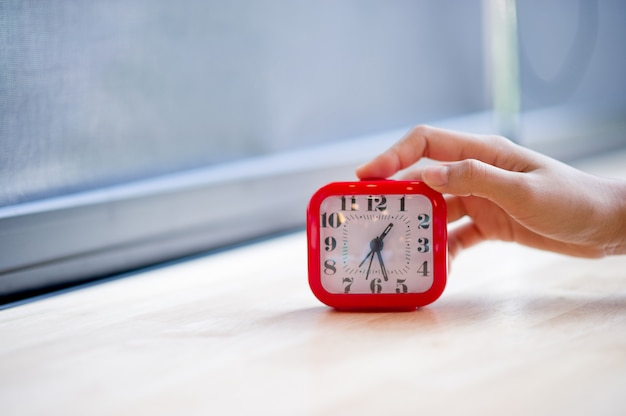 Hand and red alarm clock that shows the alarm at all every morning