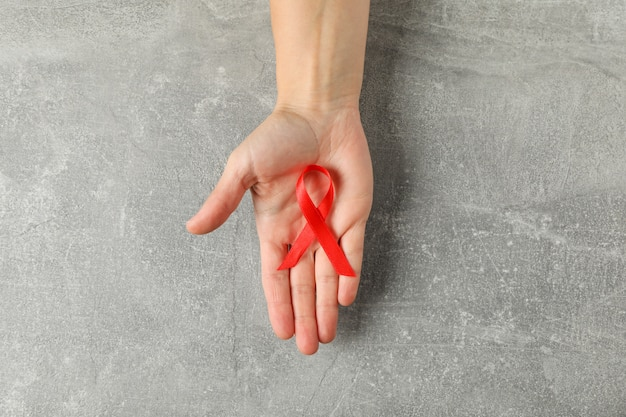 Hand and red awareness ribbon on grey wall, space for text