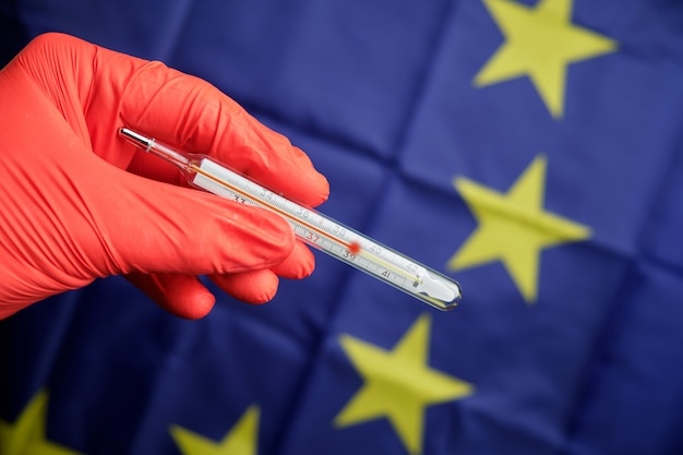 A hand in red gloves holds a thermometer with a high temperature on the background of the european union flag.