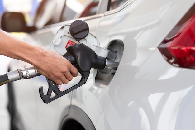 주유소에서 연료, 클로즈업, 펌핑 장비 가스로 차를 채우는 손.