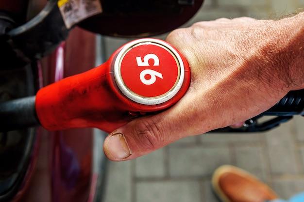 손, 승용차에 급유. 번호 95와 연료 펌프입니다. 상위 뷰입니다.