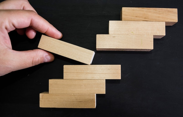 Hand removes one  wooden block on black