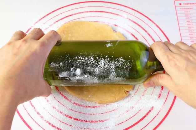 自宅で焼くアマチュア料理人の概念のための空のワインボトルと手巻きパイ生地