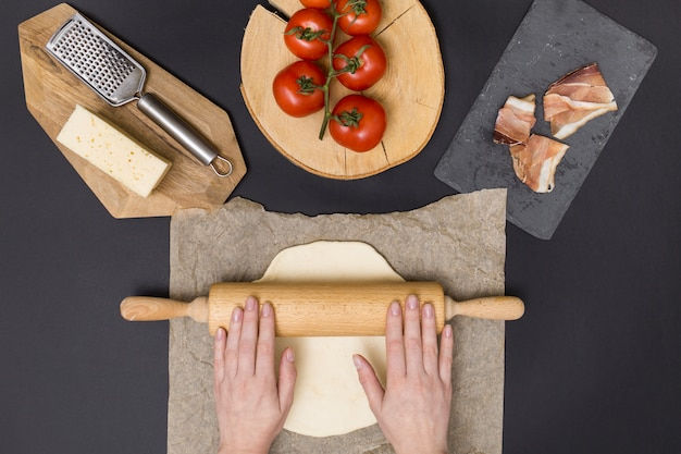 Hand rolling pizza dough on parchment paper with pizza ingredient on black background